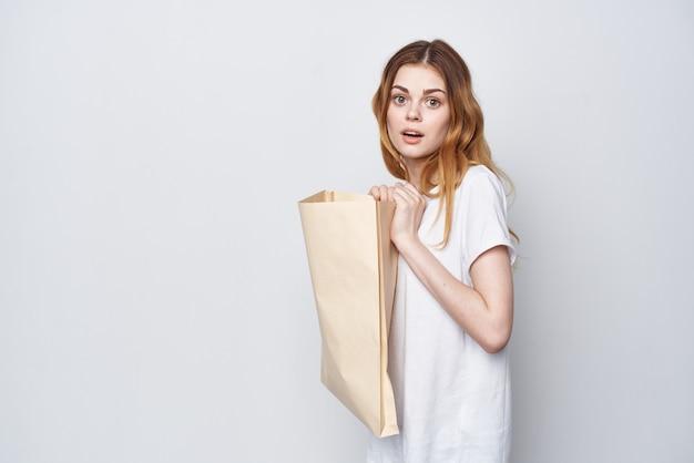 밝은 배경에서 쇼핑하는 손에 꾸러미를 들고 있는 쾌활한 여성