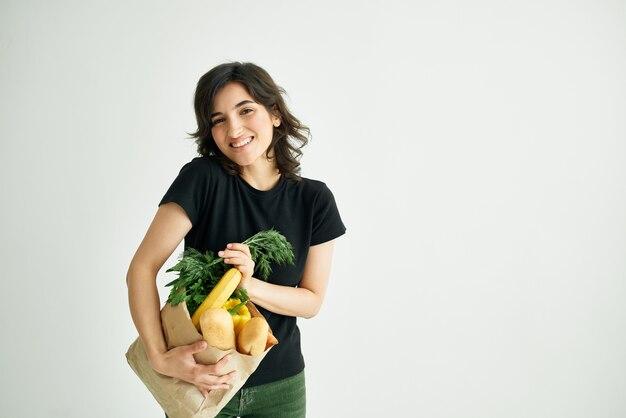 食料品の買い物のパッケージを持つ陽気な女性