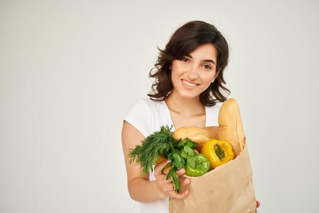 食料品スーパーマーケットの明るい背景のパッケージを持つ陽気な女性
