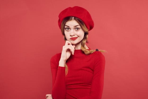 彼の頭の魅力の孤立した背景に赤いキャップを持つ陽気な女性。高品質の写真