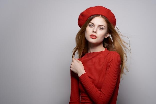 彼の頭の魅力の孤立した背景に赤いキャップを持つ陽気な女性