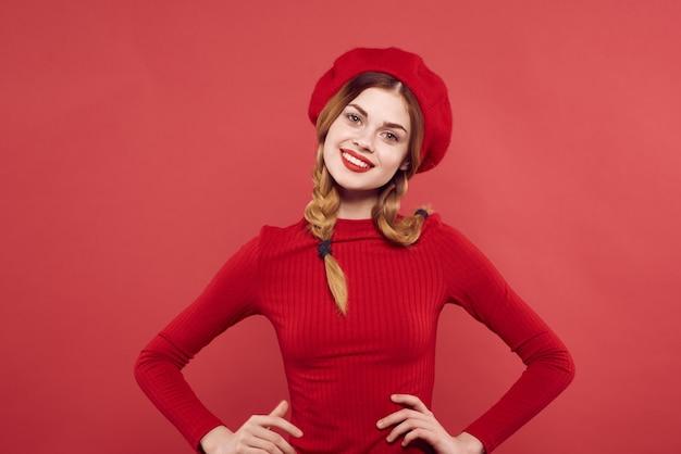 彼の頭の魅力的なスタジオのポーズに赤い帽子をかぶった陽気な女性。高品質の写真