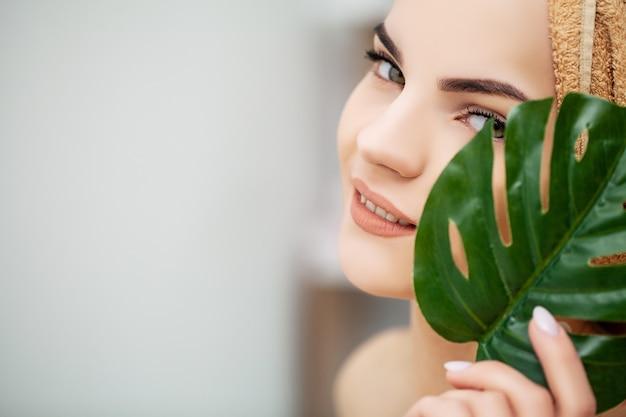 笑顔で陽気な女性は、顔の近くの花の葉を保持します