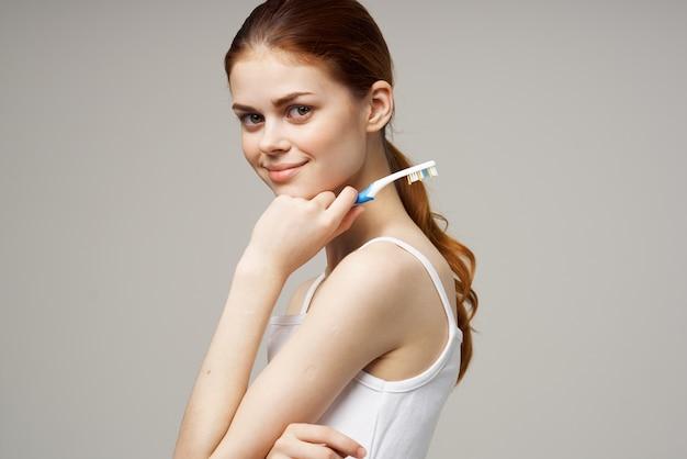 手に歯ブラシを持つ陽気な女性朝の衛生明るい背景。高品質の写真