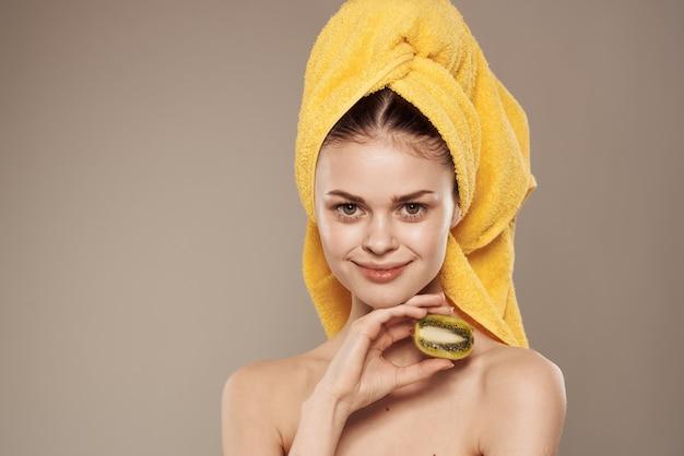 Веселая женщина с желтым полотенцем на голове с киви