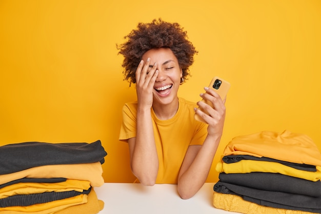 Cheerful woman with afro hair makes face palm smiles broadly holds mobile phone feels glad dressed in casual t shirt surrounded by two piles of folded clothing isolated over yellow