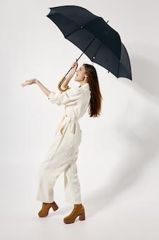 비 유행 전체 길이 의류에서 그녀의 머리 보호에 열려 우산을 가진 쾌활 한 여자. 고품질 사진