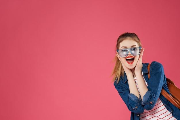 バックパックファッション感情ピンクの背景を持つ陽気な女性