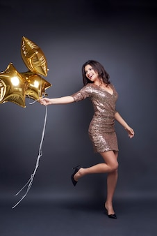 Cheerful woman with balloon at studio shot