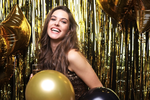 Cheerful woman with balloons laughing on gold background.
