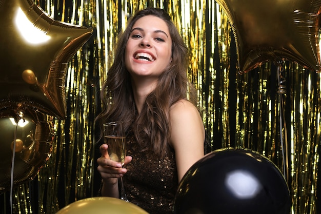 金色の背景で笑っている風船と陽気な女性。