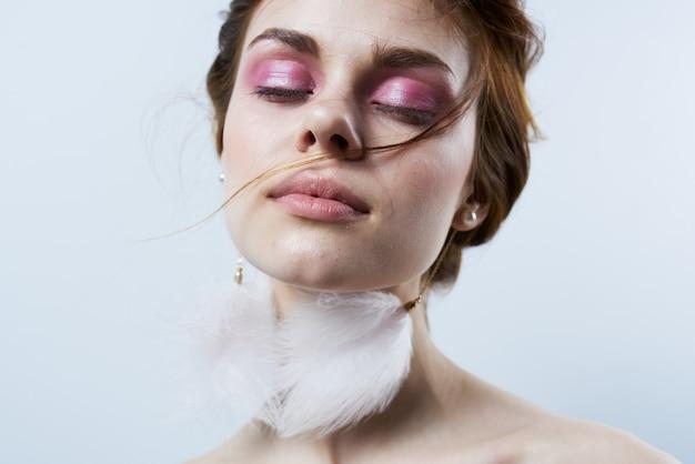 Веселая женщина с открытыми плечами пушистые серьги яркий макияж