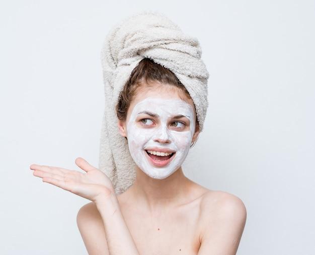 Жизнерадостная женщина с голыми плечами, жестикулирующая руками, кремовая маска для лица, эмоции.