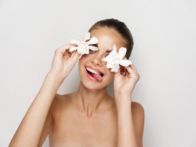 裸の肩を持つ陽気な女性は彼女の手に白い花で彼女の舌を示しています