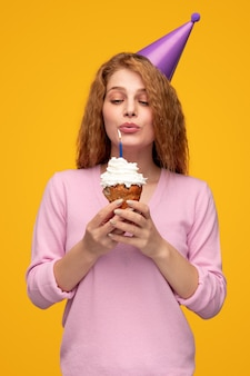 Cheerful woman with birthday cupcake