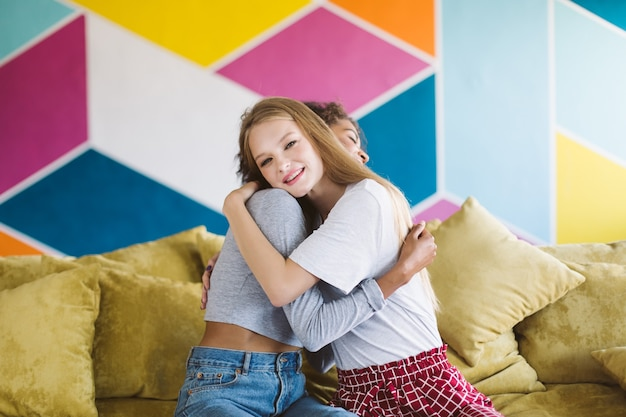 Cheerful woman with blond hair hugging girlfriend while happily  with colorful wall