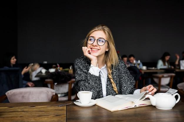 카페에서 책을 가진 쾌활 한 여자
