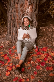 Cheerful woman with book sitting on leaves
