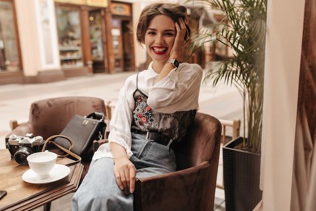 갈색 머리와 붉은 입술 레스토랑에서 웃 고 쾌활 한 여자. 블라우스와 청바지에 낙관적 인 여자는 카페에서 포즈.
