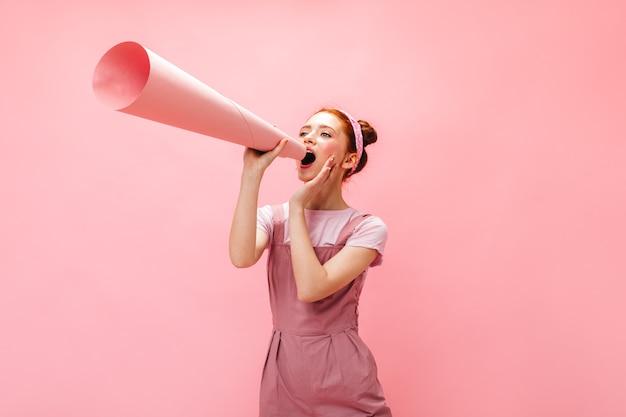 お団子を持つ陽気な女性がマウスピースに叫びます。ピンクの背景にポーズをとるオーバーオールの女性。