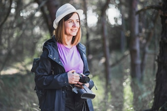 Cheerful woman with camera in forest