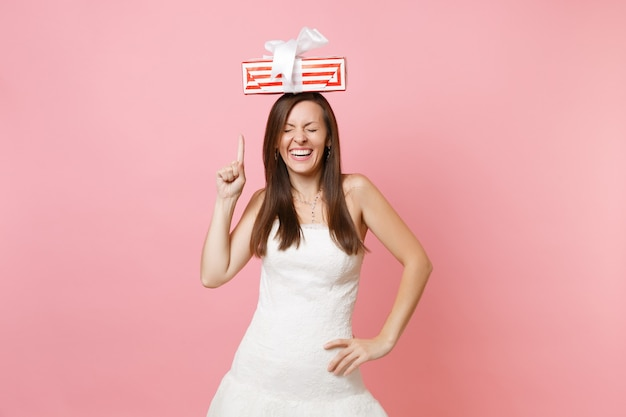 Donna allegra con gli occhi chiusi in abito bianco che punta il dito indice sulla scatola rossa con regalo presente sulla testa