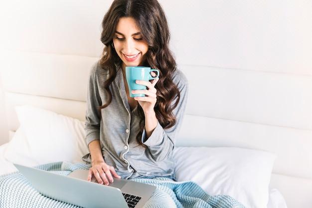 Donna allegra con la tazza al computer portatile