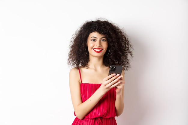 Cheerful woman with curly hair, using smartphone in red dress, smiling at camera, standing over white background. copy space