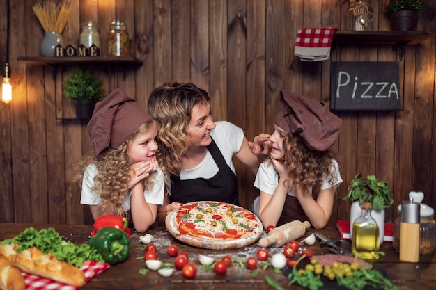 Cheerful woman with cute girls in aprons and hats smiling and looking each other during pizza preparation in kitchen at home