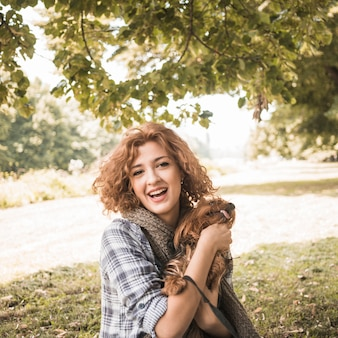 Cheerful woman with dog in park