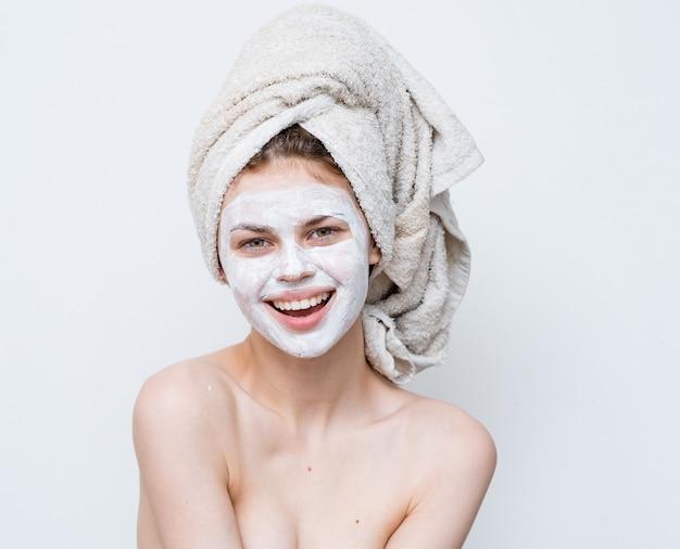 Жизнерадостная женщина с маской для лица чистая гигиена кожи голые плечи.