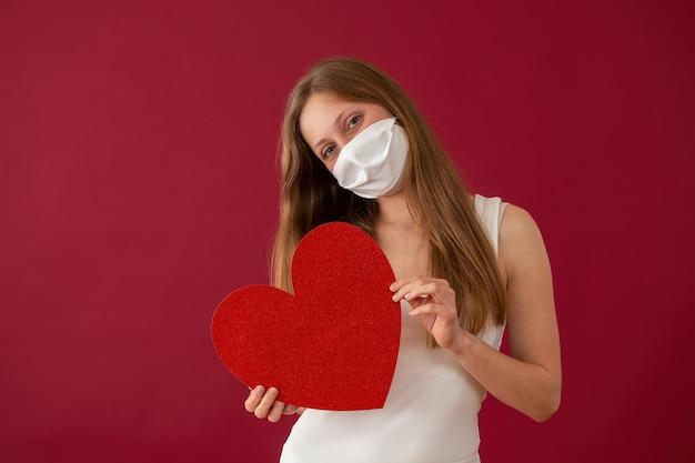正面から赤いハートを示すフェイスマスクを持つ陽気な女性。