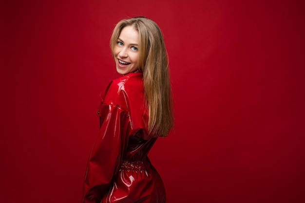 Cheerful woman with fair hair in red suit smiles, picture isolated on red background