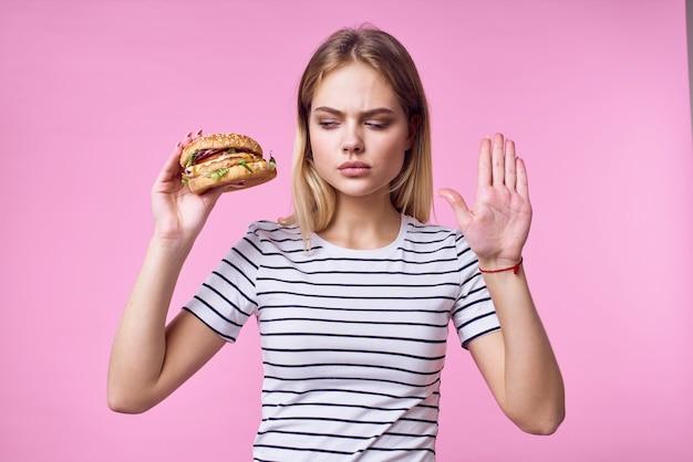 Веселая женщина с фаст-фудом в руках закуски вкусный розовый фон