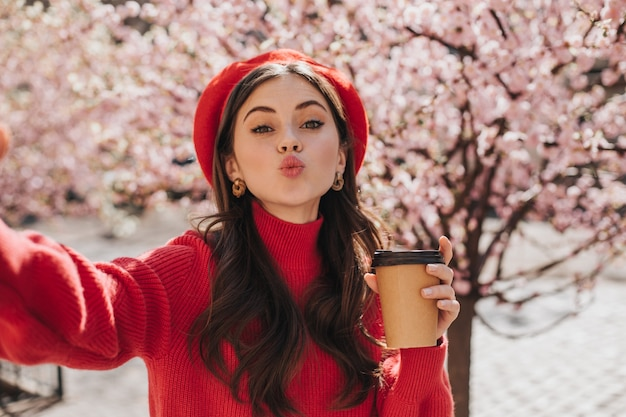 Cheerful woman with glass of tea in her hands blows kiss and takes selfie. portrait of lady in red sweater holding coffee cup against blooming sakura