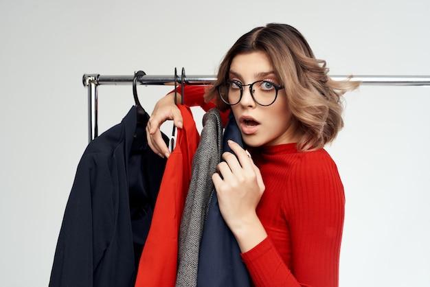 Веселая женщина в очках рядом с одеждой, модные забавные эмоции