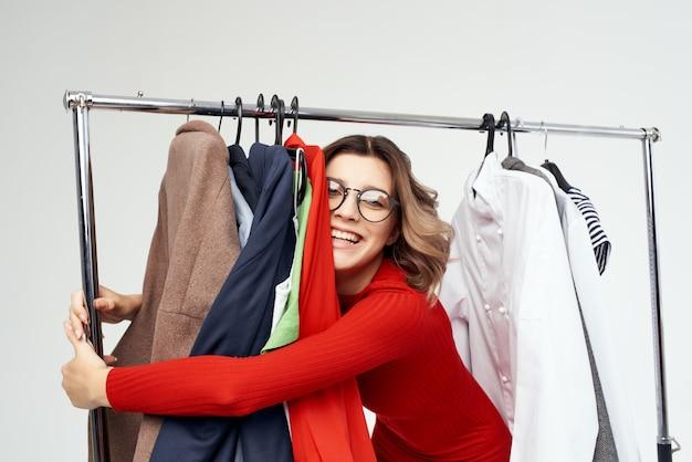 옷 옆에 안경을 쓴 쾌활한 여성 패션 재미 고립 된 배경. 고품질 사진