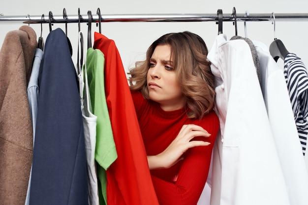 Веселая женщина в очках выбор одежды возле гардеробной студии образа жизни