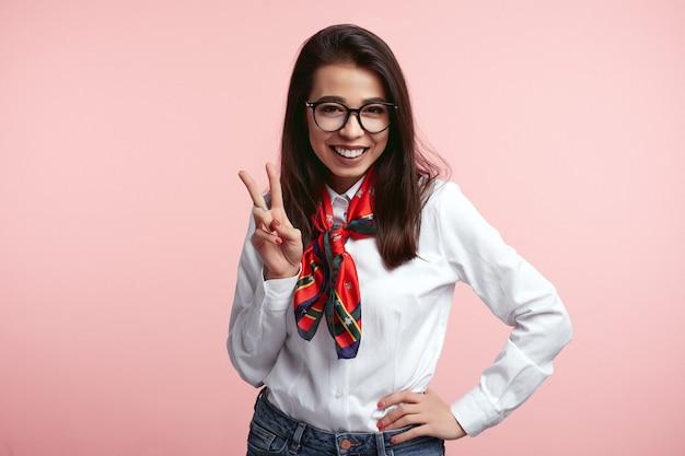 Веселая женщина в очках показывает жест мира над розовой стеной