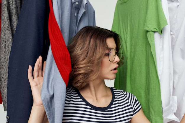 안경을 쓴 쾌활한 여성이 옷가게 소매에서 격리된 배경을 시도하고 있습니다.