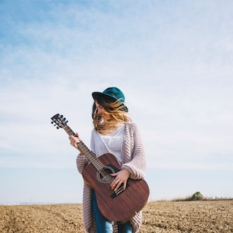 Веселая женщина с гитарой в сельской местности