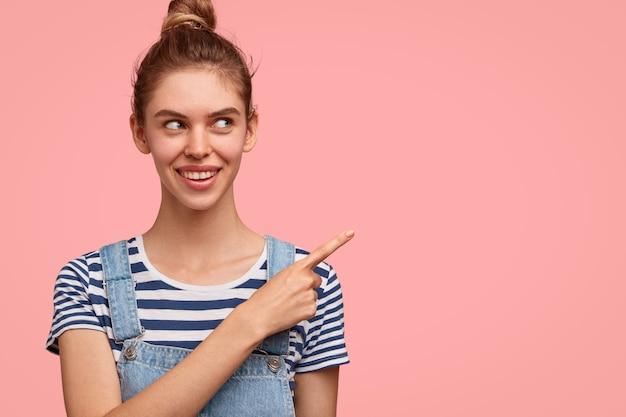 カジュアルな服装で、髪のお団子を持つ陽気な女性