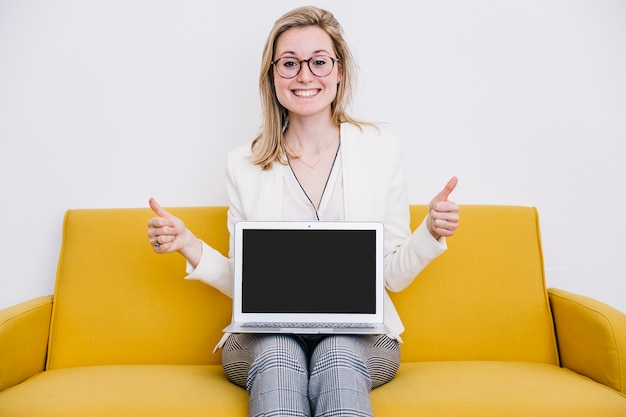 Cheerful woman with laptop gesturing thumb-up