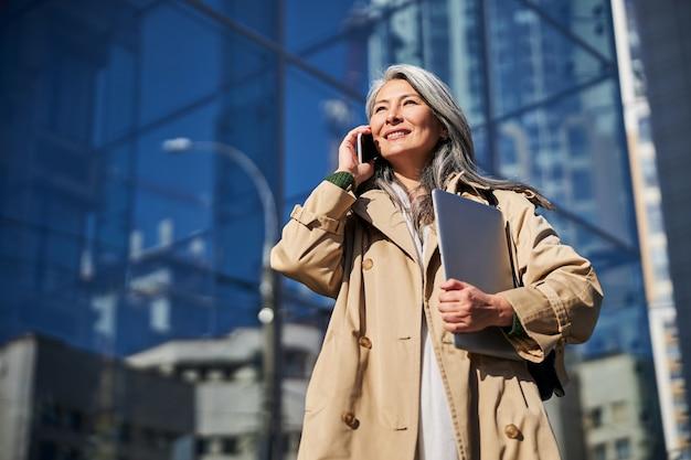 屋外で電話で会話するラップトップを持つ陽気な女性