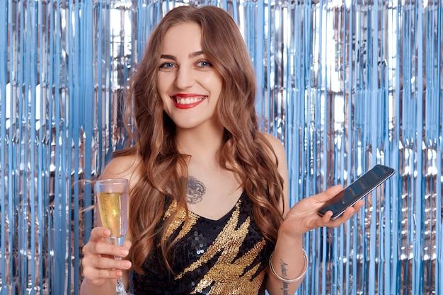長い巻き毛を持つ陽気な女性、黒のドレスでファッショナブルな女の子は、シャンパンを飲み、スペースに銀色にキラキラ見掛け倒しの青い壁に電話を保持しています。