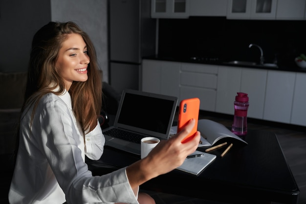 Cheerful woman with long hair doing selfie on modern smartphone while staying at home