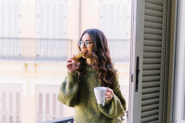 Cheerful woman with mug eating croissant