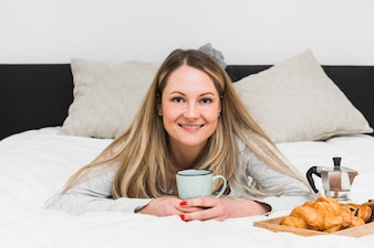 Cheerful woman with mug on bed