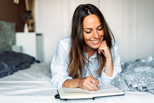 Cheerful woman with notebook and pen smiling while resting on bed