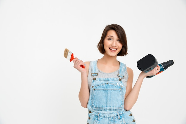 Cheerful woman with painting brush and hand drill